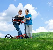 A caregiver guides a young boy in a Dynamic Pacer gait trainer in an outdoor setting