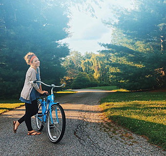 Karlie Pickett stands by her bicycle waiting for her brother with cerebral palsy on his special needs tricycle.