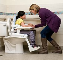 A therapist positions a child with physical disabilities on the toilet using adaptive toileting supports.