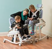 A therapist with two children sitting shower commode chair adjusted to match their special needs.