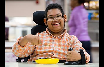 A young boy in a wheelchair using a Rifton Anchor at a school cafeteria table.