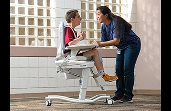A caregiver positions a school-aged boy in the Rifton HTS adaptive toilet and shower seat.