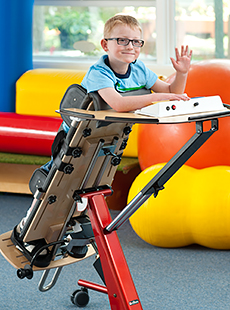 A small boy waves for the camera while standing in a Rifton Prone stander