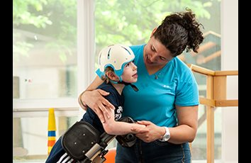 A small boy leans forward in a Rifton Prone stander without a tray, while his caregiver puts her arm around him