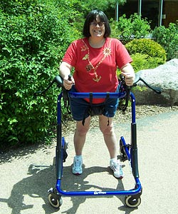 A smiling woman practices gait training outdoors in the sun. She is moving forward in her Rifton gait trainer, which offers more support than any other 4 wheeled walker .