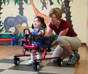 A therapist helps position a young girl to be a walker in a mini Rifton Pacer Gait Trainer