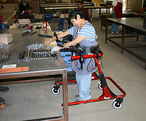 Movement disorders don't stop this woman from assembling parts in a warehouse space in a Rifton gait trainer