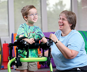 A young boy movement disorders is led by a smiling therapist as he walks in a Rifton gait trainer.