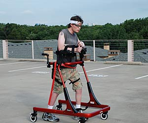 Sean Carter is a walker, moving across a parking lot in his Rifton Pacer gait trainer