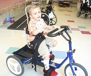 David riding a blue Rifton tricycle at a pediatric cancer survival rehab center