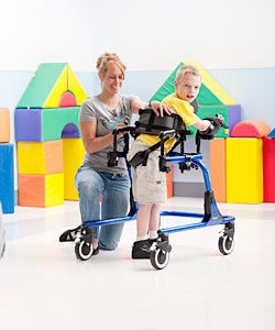 A young boy in a pediatric gait trainer is instructed by a woman kneeling by his side on how to use the device.