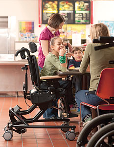 A young girl in a cafeteria eating lunch in a Rifton active sitting chair