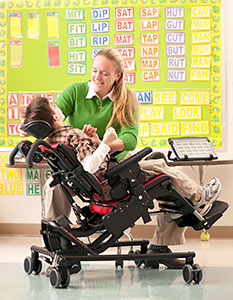 A young boy in a classroom, tilted back in a Rifton adaptive seating chair, smiles at his caregiver who is holding his hand