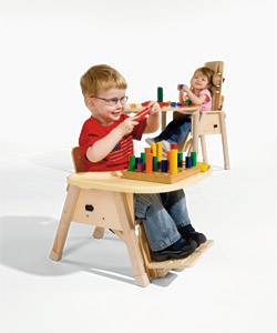 A young boy and girl demonstrating proper positioning in the Rifton Chair, smile as they play with colorful toys