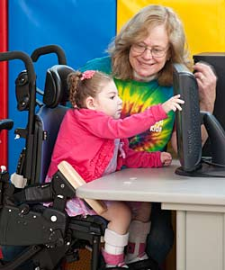 A Young Girl in an Activity Chair Pushes a Screen with the Aide of a RTS Device While a Smiling Woman Assists Her