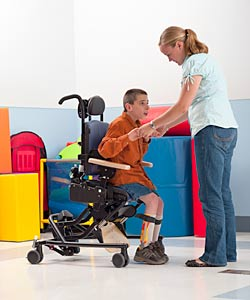 Rifton Chairs woman helps a young boy out of his Rifton special needs chair in a ...