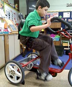 A young boy exercising on his adaptive tricycle in the classroom thanks to the Rifton stationary bike stand.