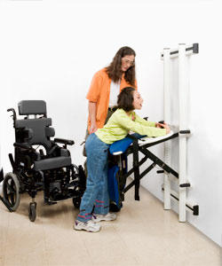 A therapist helps a young girl in a wheelchair transfer to a disabled changing table for toileting