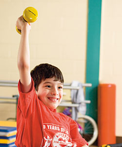 A young boy with cerebral palsy exercises by lifting a yellow hand weight up in the air