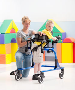 A woman therapist helps a young boy with disabilities into a Pacer gait trainer