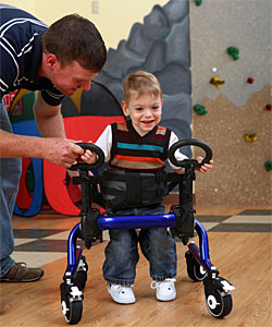 A toddler, with the help of a therapist, practices control in a gait trainer while learning functional motor skills