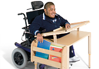 A teenage boy sits in his wheelchair at a desk designed for complex rehab and with multi-use technology