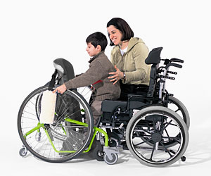 A woman assists a young boy from a wheelchair to an adaptive stander for motor skills training