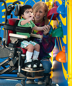 A young boy with Rett Syndrome, grabs with awe at a bell, while being tilted forward in his Rifton Activity Chair by a young woman.