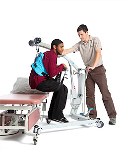 A therapist practices safe patient lifting by transferring a young man from a treatment table using Rifton SoloLift equipment