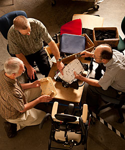 An overhead shot of a team of 3 men gathering at a table to discuss special needs design for a new product