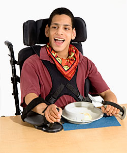 A young man in a Rifton chair uses arm stabilizers to assist him with improving his functional ability so he can participate in mealtime