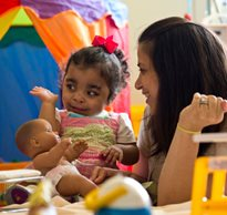 A therapist and daughter in a playroom, both smiling, as the little girl waves while playing with a doll