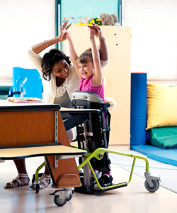 A classroom setting with a therapist and a young girl in a Dynamic Stander raising their hands up cheering and smiling showing the benefits of standing.