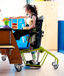 A young girl in a classroom setting can participate in classroom activities when in her standing device frame.