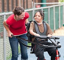A caregiver smiles as she leans over helping a young girl with her special needs equipment