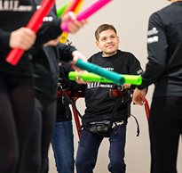 A young man with disabilities in a gait trainer smiles as he performs his dance movements
