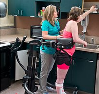 A therapist assists a CNS patient who is standing in a TRAM device practicing gait training during rehabilitation.