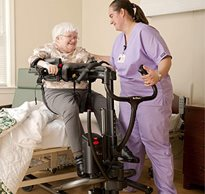 A therapist uses a Rifton TRAM to safely handle a patient moving them from a seated position on a hospital bed to a standing and mobile position.