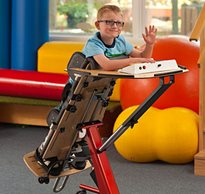 A young boy in a Prone stander gives a wave as he participates in classroom activities.