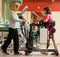 Guided by a therapist, a women with a prosthetic limb uses the multi-tasking Rifton TRAM device to assist in walking.