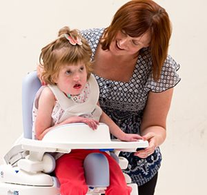 Using recommended guidelines, a therapist properly positions a child with special needs on the Rifton Hygiene Toileting System.