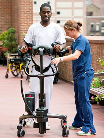 A patient walks in the Rifton TRAM assisted by a caregiver after using it to perform a sit to stand transfer