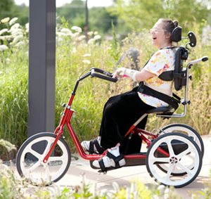 A patient demonstrates equipment positioning while smiling and riding on a red tricycle.