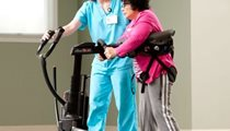 A therapist guides a home care patient in a stand-pivot transfer using the Rifton TRAM