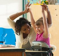 A girl with cerebral palsy smiles while her caregiver lifts her arms into the air.