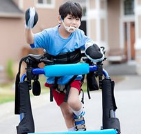 A young boy in an over-ground gait trainer smiles as he walks down the driveway