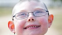A young boy with disabilities looks up at the sky with a big smile