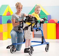 A therapist refers to a checklist to position a young boy in his Pacer gait trainer