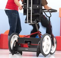 A therapist works with a special needs teen who is pedaling away indoors on a stationary trike