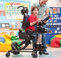 A therapist is teaching a special needs student active sitting and positioning in a Rifton Activity Chair in a classroom setting